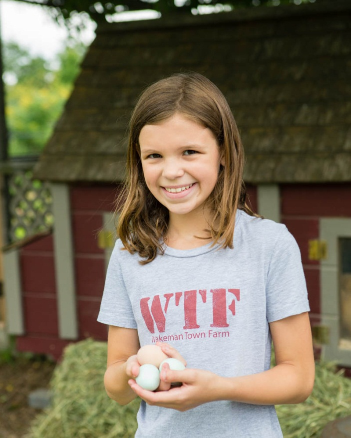 Child smiling while holding eggs from farm